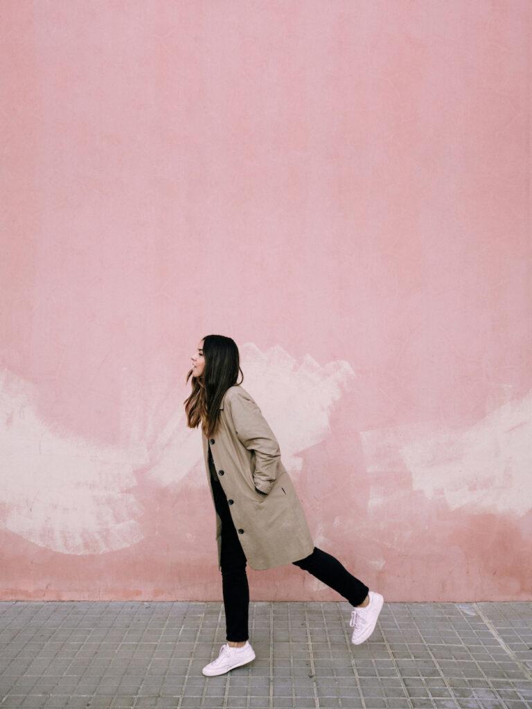 Carol Peña caminando frente a fondo rosado, Foto de creadora de contenido atípica y exitosa - Carol Peña